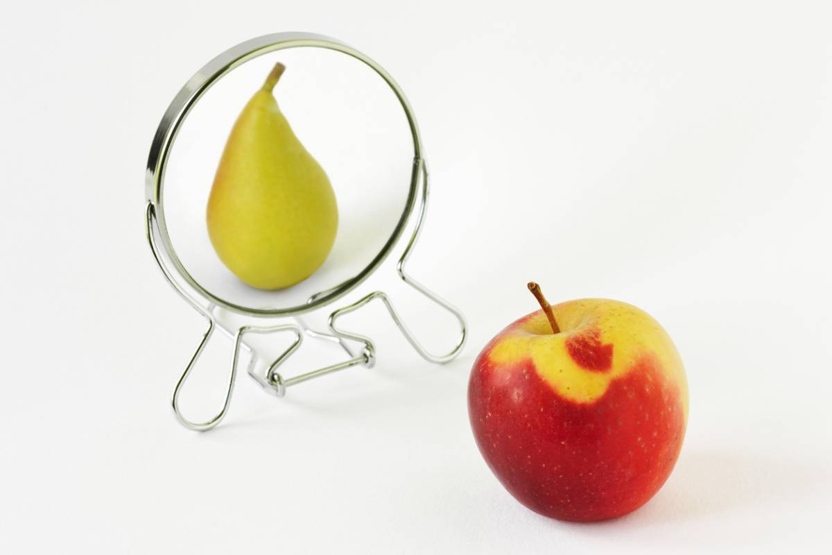 Apple looking at itself as a pear in a mirror (metaphor for body dysmorphia)
